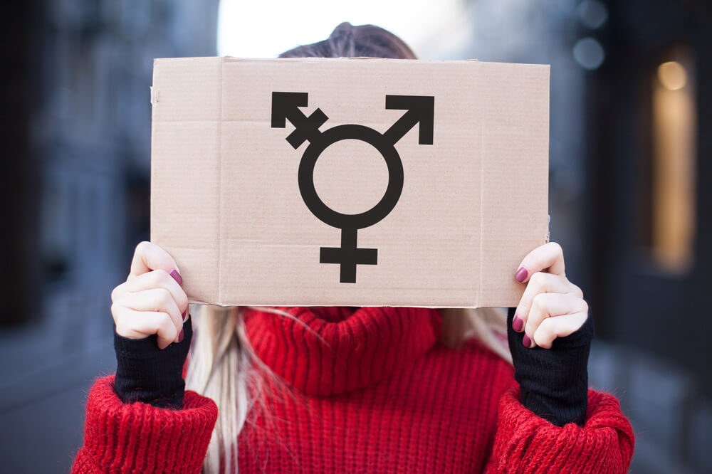 Woman in red holding a three genders' sign