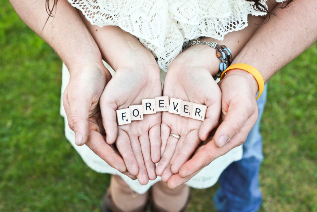 couple holding hands and forming the the word 'forever' with scrabble pieces.