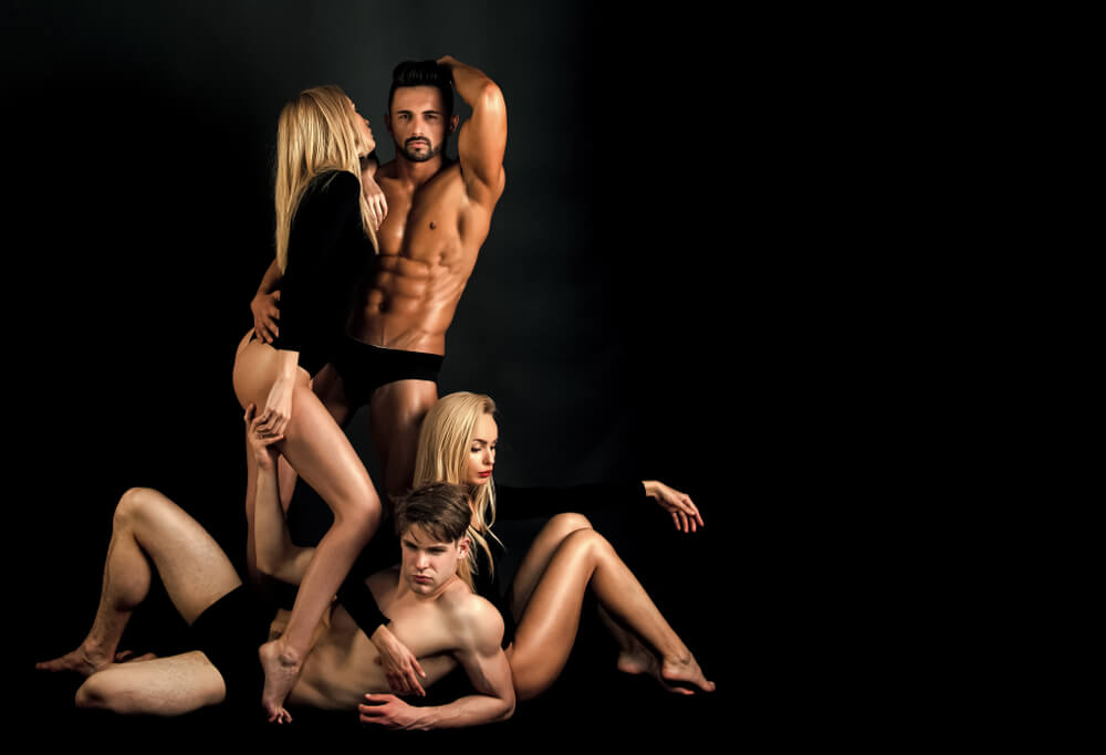 Two blonde women and two dark haired men are posing together, preparing for a swinger's party