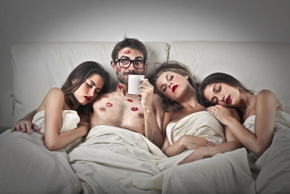 A guy with three beautiful women lying in bed. The man has kissing marks on his face and chest.