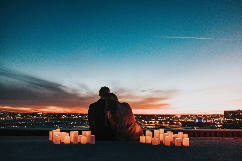 Couple sitting on a roof in candlelight while the sun sets