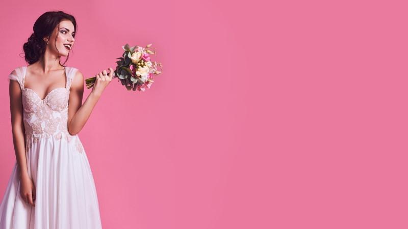 pretty brunette bride in wedding dress showing off her bridal bouquet